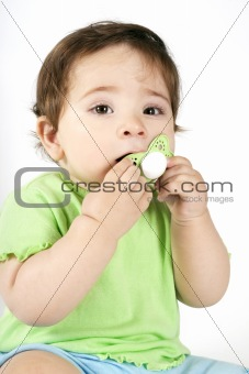 Baby putting a dummy into mouth