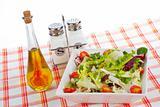 Oil bottle, green salad, salt and pepper