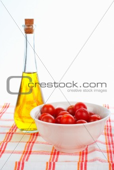 Olive oil bottle and red tomatos cherry