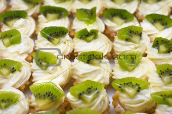 Small cakes (petit four) with custard and kiwi on top. Shallow DOF. Sharp focus on second line.