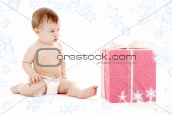 baby boy in diaper with big gift box and snowflakes
