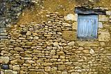 Old yellow stone wall with close window
