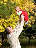 father playing with son in autumn park