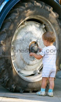 little boy near big truck wheel