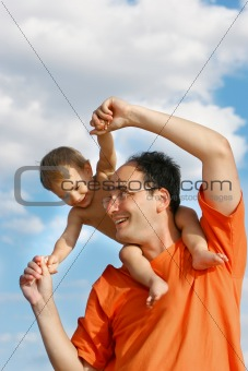 father playing with son over sky background