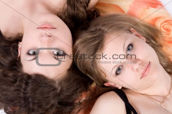 Portrait of the two beauty young women laying on a pillow 1