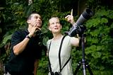 Pretty Woman with Binoculars and Man with Telescope in Jungle