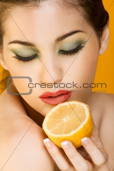 Beautiful woman with half of lemon, closed eyes