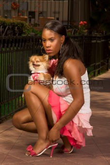 Black woman squatting, with Pomeranian Spitz dog
