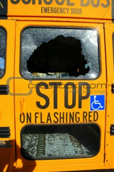 a broken window in the back of a school bus