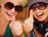Closeup of happy young girls showing thumb&#39;s up sign