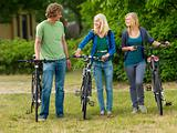 Young guys and girls with bicycle in the nature field