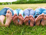 Feet of teenagers lying on green field