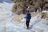 Man snowshoer climbing hill