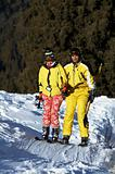 Yong family skiers in yellow rise on ski lift