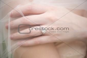 Bride's wedding ring underneath a veil