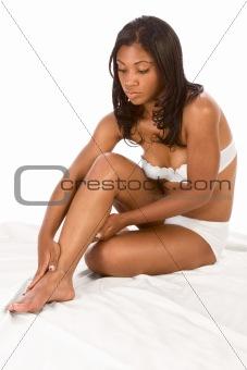 Beautiful black girl applies moisturizer on legs