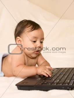 Baby boy checking e-mail on his parents laptop