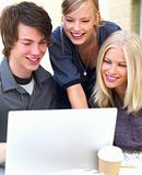 Happy young friends using laptop
