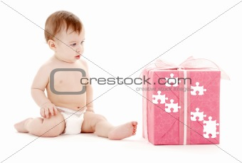 baby boy in diaper with big puzzle gift box