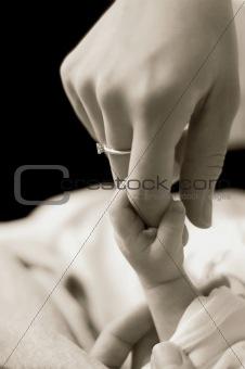 Baby holding mum's finger