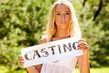 "Young blond woman holding a sign ""casting"" outdoors"