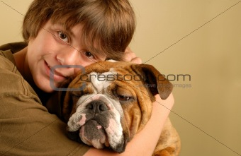boy hugging english bulldog