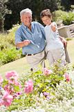Grandfather and grandson outdoors in garden pointing at plants a