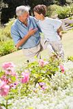 Grandfather and grandson outdoors in garden talking and smiling