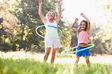 Grandmother and granddaughter at a park hula hooping and smiling