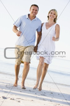 Couple at the beach holding hands and smiling