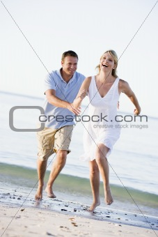 Couple at the beach playing and smiling