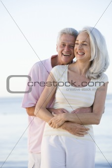 Couple at the beach embracing and smiling