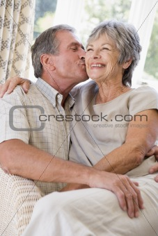 Couple relaxing in living room kissing and smiling