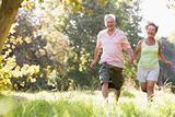 Couple running in park holding hands and smiling