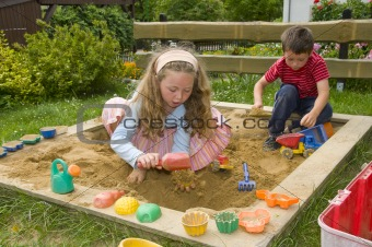boy and girl playing in sand box