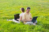 Coupe sitting with laptops in a meadow