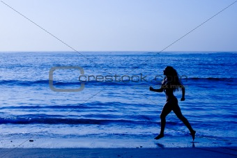 Healthy life concept - sporty woman running along beach
