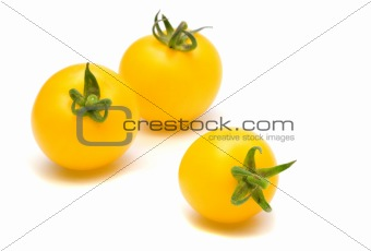 three yllow tomatoes on white background
