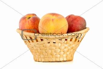 Three tasty peaches in wicker basket