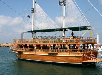 Pirate Ship under sail with the shore in the background
