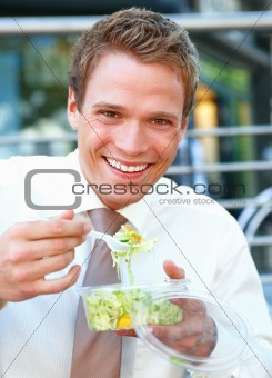 Portrait of happy young businessman eating salad