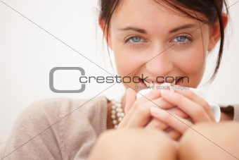 Happy young woman holding  cup against isolated white background