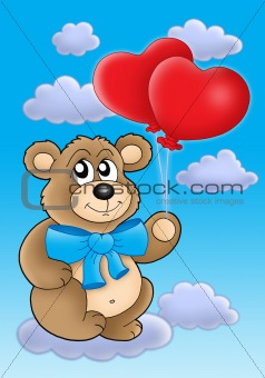 Teddy bear with heart balloons on blue sky