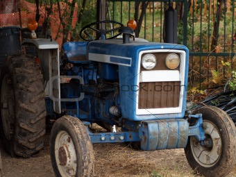 Old blue tractor in the shed with mud