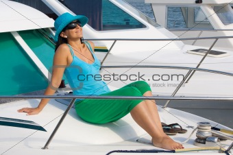 beautiful woman aboard a yacht sunbathing