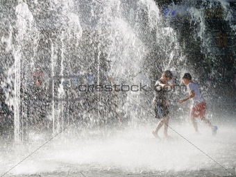 Boys playing in sprinkling water