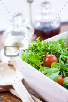 Green salad with tomatoes and a wooden spoon