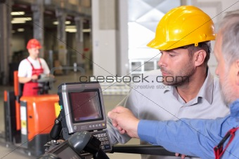 male engineer talking to forklift operator