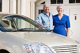 Senior couple standing to new car